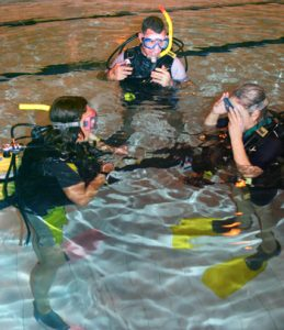 Trainees learn to dive with an instructor in a safe pool setting